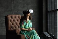 Das VR-Kopfhörerdesign ist generisch und keine Logos, Frau mit Gläsern virtueller Realität, sitzt in einem Stuhl, gegen einen dun stockfotos