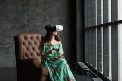Das VR-Kopfhörerdesign ist generisch und keine Logos, Frau mit Gläsern virtueller Realität, sitzt in einem Stuhl, gegen einen dun lizenzfreie stockfotografie