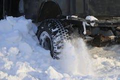 Das Wagenrad ist im Schnee fest Spray des Schnees vom drehenden Rad des Winters ermüdet Gleiten der Maschine im Schnee Th lizenzfreies stockfoto