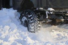 Das Wagenrad ist im Schnee fest Spray des Schnees vom drehenden Rad des Winters ermüdet Gleiten der Maschine im Schnee Th lizenzfreie stockfotografie