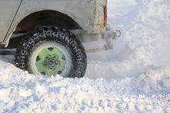 Das Wagenrad ist im Schnee fest Spray des Schnees vom drehenden Rad des Winters ermüdet Gleiten der Maschine im Schnee Th stockbilder
