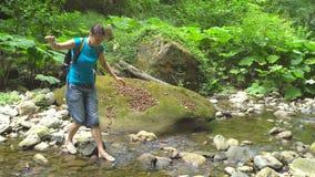 Das Wandern der Schönheit mit den balancierenden Händen des Rucksacks kreuzt einen Gebirgsfluss mit großen Flusssteinen und grüne stock footage