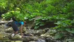 Das Wandern der Schönheit mit Rucksack hockend kreuzt einen Gebirgsfluss mit großen Flusssteinen und grünem Moos im Dschungel stock video footage