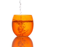Das Wasser, das in schönes orange Farbglas gegossen wird - spritzt Isolator Stockfoto