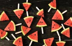 das Wassermelonenscheibeneis am stiel auf einem rustikalen hölzernen Hintergrund Lizenzfreies Stockbild