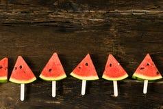 das Wassermelonenscheibeneis am stiel auf einem rustikalen hölzernen Hintergrund exemplar Stockfotos