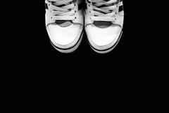Das Weiß trägt Schuhe auf einem Hintergrund zur Schau Lizenzfreies Stockfoto