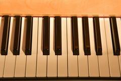 Das weiße Elfenbein und die schwarzen Tasten eines Klaviers Stockfotografie
