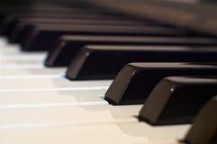 Das weiße Elfenbein und die schwarzen Tasten eines Klaviers stockbilder