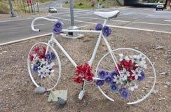 Das weiße Fahrrad, das mit blauer und roter Blume verziert wird, formt an in Stockfoto