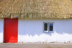 Das Weiße Haus deckte Red Roof mit Stroh Stockfotos