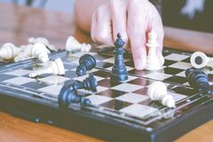 Das weiße Schach auf Frauenhand kämpft mit Schwarzem, denken, sich besprechen, festgelegt, Wettbewerb, der Sieger, erfolgreich, e stockfoto