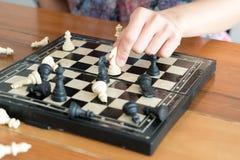 Das weiße Schach auf Frauenhand kämpft mit Schwarzem, denken, sich besprechen, festgelegt, Wettbewerb, der Sieger, erfolgreich, e lizenzfreies stockfoto
