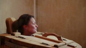 Das weibliche Haupthaften aus der Zeder heraus rast an einem Badekurortsalon Blondine führen Dampfverfahren für die Wiederaufnahm stock footage