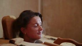 Das weibliche Haupthaften aus der Zeder heraus rast an einem Badekurortsalon Blondine führen Dampfverfahren für die Wiederaufnahm stock video
