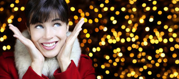 Das Weihnachtsfrauenlächeln schaut oben im Lichthintergrund Stockfotos