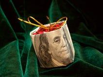 Das Weihnachtsspielzeug eingewickelt im Dollarschein Lizenzfreie Stockfotos