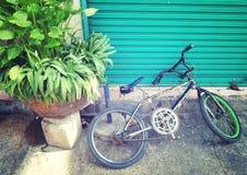 Das Weinlese-Fahrrad, das in der blauen Tür der alten Straße mit Weinlese stillsteht, rösten Stockbilder