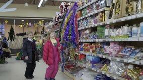 Das wenig nette Mädchen- und Jungenwählen verzieren für Weihnachten-Baum im Einkaufszentrum stock video footage