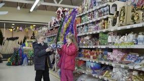 Das wenig nette Mädchen- und Jungenwählen verzieren für Weihnachten-Baum im Einkaufszentrum stock footage