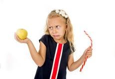Das wenig recht weibliche Kind, das den Nachtisch hält ungesundes aber geschmackvolles rotes Süßigkeitssüßholz und -apfel wählt,  Stockfotografie