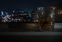 Das Whiskyglas wird neben dem Fenster in das Hotelzimmer gelegt lizenzfreie stockfotografie