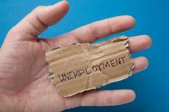 Das Wort 'Arbeitslosigkeit 'auf der heftigen alten Pappe in der Hand eines Mannes stockfotos