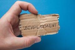 Das Wort 'Arbeitslosigkeit 'geschrieben auf Pappe in die Hand des Mannes, lokalisiert auf einem blauen Hintergrund, Verzweifl stockbild