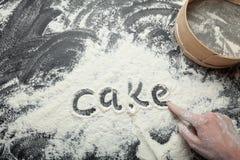 Das Wort 'Kuchen 'wird auf den Hintergrund des Mehls von der Hand einer Frau geschrieben lizenzfreie stockfotos