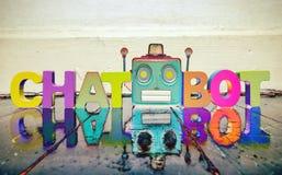 Das Wort CHAT BOT mit einem roten Roboterkopf auf einem Bretterboden lizenzfreie stockbilder