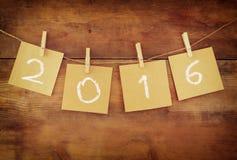 Das Wort 2016, das auf Wäscheklammer geschrieben wurde, befestigte Karten vor hölzernem Hintergrund Stockfotografie