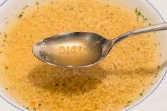 Das Wort diat mit Buchstaben einer Buchstabesuppe auf einem Löffel lizenzfreie stockfotografie