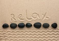Das Wort entspannen sich geschrieben auf den Sand Lizenzfreies Stockfoto