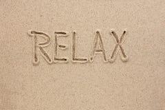 Das Wort entspannen sich geschrieben auf den Sand Stockfotos