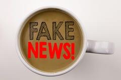 Das Wort, gefälschte Nachrichten schreibend simsen im Kaffee in der Schale Geschäftskonzept für Propaganda-Zeitungs-Fälschungs-Na lizenzfreies stockbild