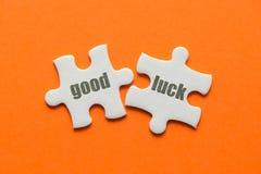 Das Wort gute Glück auf zusammenpassendem Puzzlespiel zwei auf orange Hintergrund stockbild