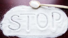Das Wort HALT auf dem Tisch geschrieben auf einen bedeckten Zucker und einen hölzernen Löffel Stockfotos