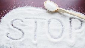 Das Wort HALT auf dem Tisch geschrieben auf einen bedeckten Zucker und einen hölzernen Löffel Stockbilder