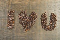 Das Wort ich liebe dich gemacht von den Kaffeebohnen auf Holztisch Stil Stockfoto