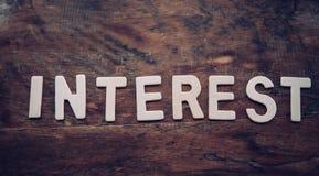 Das Wort ` INTERESSE ` wird von einem hölzernen Buchstaben vereinbart, der auf einen Bretterboden gesetzt wird lizenzfreies stockbild