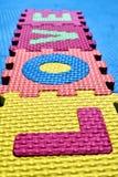 Das Wort LIEBE geschrieben mit einem Puzzlespiel der bunte Kinder mit Buchstaben lizenzfreies stockfoto