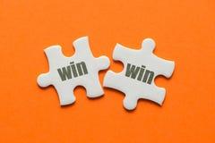 Das Wort mit Gewinn für beide Parteien auf zusammenpassendem Puzzlespiel zwei auf orange Hintergrund lizenzfreies stockbild