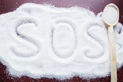 Das Wort PAS auf dem Tisch geschrieben auf einen bedeckten Zucker und einen hölzernen Löffel Stockfoto