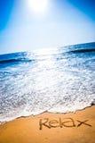 Das Wort RELAX geschrieben in den Sand auf einen Strand Lizenzfreies Stockfoto