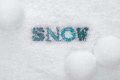 Das Wort SCHNEE auf einem Schneehintergrund Lizenzfreie Stockfotos