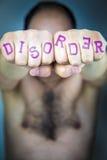 Das Wort STÖRUNG geschrieben auf die Fäuste eines Mannes lizenzfreies stockfoto