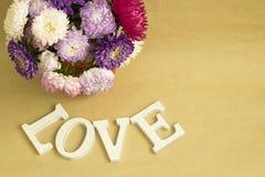 Das Wort u. das x22; love& x22; und ein Blumenstrauß von Blumen Stockfoto