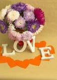 Das Wort u. das x22; love& x22; und ein Blumenstrauß von Blumen Stockbilder