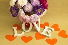 Das Wort u. das x22; love& x22; und ein Blumenstrauß von Blumen Lizenzfreie Stockfotos