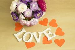 Das Wort u. das x22; love& x22; und ein Blumenstrauß von Blumen auf einem Hintergrund des braunen Kraftpapiers Stockfotografie